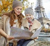 Ευτυχείς τουρίστες μητέρων και κορών που εξετάζουν το χάρτη στο Παρίσι Στοκ εικόνες με δικαίωμα ελεύθερης χρήσης