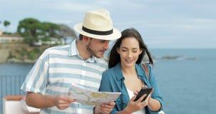 Ευτυχείς τουρίστες που περπατούν συγκρίνοντας το τηλέφωνο και το χάρτη στην παραλία απόθεμα βίντεο
