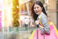Ευτυχείς τσάντες και ένδυση αγορών εκμετάλλευσης κοριτσιών smartwatch Στοκ φωτογραφίες με δικαίωμα ελεύθερης χρήσης