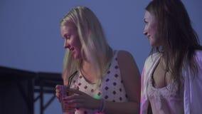 Ευτυχείς φίλες που πίνουν τα κοκτέιλ σε ένα νυχτερινό κέντρο διασκέδασης Δύο κορίτσια κάθονται με τα κοκτέιλ και κουβεντιάζουν στ απόθεμα βίντεο
