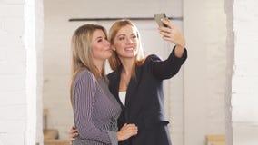 Ευτυχείς φίλες που παίρνουν τη φωτογραφία με το κινητό τηλέφωνο στον καφέ φιλμ μικρού μήκους