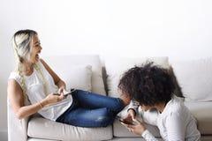 Ευτυχείς φίλες που χρησιμοποιούν το smartphone μαζί στο σπίτι στοκ φωτογραφίες