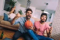 Ευτυχείς φίλοι ή ανεμιστήρες καλαθοσφαίρισης που προσέχουν το παιχνίδι καλαθοσφαίρισης στη TV Στοκ φωτογραφίες με δικαίωμα ελεύθερης χρήσης