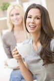 Ευτυχείς φίλοι γυναικών που πίνουν το τσάι ή τον καφέ Στοκ φωτογραφία με δικαίωμα ελεύθερης χρήσης