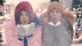 Ευτυχείς φίλοι γυναικών που φυσούν το χιόνι στο χειμώνα, σε αργή κίνηση απόθεμα βίντεο