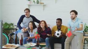 Ευτυχείς φίλοι με τις πορτογαλικές σημαίες που προσέχουν το αθλητικό πρωτάθλημα στη TV μαζί στο σπίτι και ευχαριστημένος από τη ν απόθεμα βίντεο