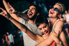 Ευτυχείς φίλοι που έχουν τη διασκέδαση στο φεστιβάλ μουσικής στοκ φωτογραφίες