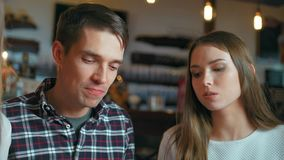 Ευτυχείς φίλοι που κάθονται στον καφέ τρώγοντας και πίνοντας το οινόπνευμα απόθεμα βίντεο