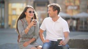 Ευτυχείς φίλοι που πίνουν τη συνεδρίαση καφέ στον πάγκο στο τετράγωνο πόλεων κατά τη διάρκεια της ηλιόλουστης θερινής ημέρας απόθεμα βίντεο