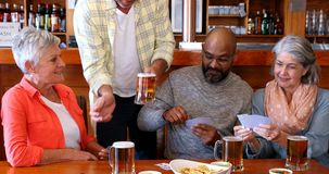 Ευτυχείς φίλοι που παίζουν τις κάρτες ενώ έχοντας το ποτήρι της μπύρας 4k απόθεμα βίντεο