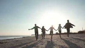 Ευτυχείς φίλοι που τρέχουν στην ακτή φιλμ μικρού μήκους