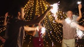 Ευτυχείς φίλοι που χορεύουν με το κόμμα sparklers τη νύχτα απόθεμα βίντεο