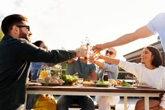 Ευτυχείς φίλοι που ψήνουν τα ποτά στο κόμμα στεγών στοκ φωτογραφίες
