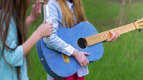 Ευτυχείς φίλοι σε μια ζώνη, που τραγουδά και που παίζει μια ακουστική κιθάρα στο πάρκο απόθεμα βίντεο