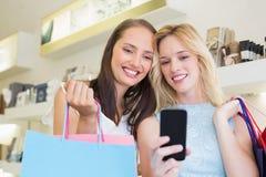 Ευτυχείς φίλοι γυναικών που εξετάζουν το smartphone στοκ φωτογραφία με δικαίωμα ελεύθερης χρήσης