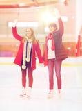 Ευτυχείς φίλοι κοριτσιών που κυματίζουν τα χέρια στην αίθουσα παγοδρομίας πατινάζ Στοκ Εικόνες