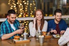 Ευτυχείς φίλοι με τα smartphones στο εστιατόριο Στοκ Φωτογραφίες