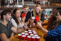 Ευτυχείς φίλοι που πίνουν την μπύρα καθμένος τα μίας χρήσης φλυτζάνια στο φραγμό Στοκ Φωτογραφία