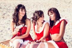 Ευτυχείς φίλοι στα καπέλα santa στην παραλία τα Χριστούγεννα σύνδεσαν την κενή ειδικά εικόνα γραφείων lap-top Διαδικτύου βιομηχαν Στοκ Φωτογραφία