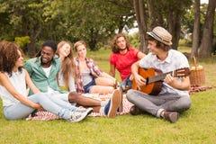 Ευτυχείς φίλοι στο πάρκο που έχει το πικ-νίκ Στοκ φωτογραφία με δικαίωμα ελεύθερης χρήσης