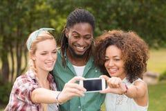 Ευτυχείς φίλοι στο πάρκο που παίρνει selfie Στοκ εικόνα με δικαίωμα ελεύθερης χρήσης