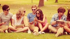 Ευτυχείς φίλοι στο πάρκο που χρησιμοποιεί τις ηλεκτρονικές συσκευές απόθεμα βίντεο