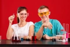Ευτυχείς φιάλες εργαστηριακών δύο βοηθητικές χαμόγελου και κρατήματος με το πολύχρωμο υγρό Σε μια κόκκινη ανασκόπηση Στοκ Εικόνες