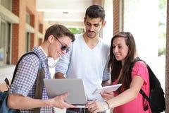 Ευτυχείς φοιτητές πανεπιστημίου που χρησιμοποιούν τον υπολογιστή Στοκ εικόνα με δικαίωμα ελεύθερης χρήσης