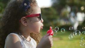 Ευτυχείς φυσαλίδες σαπουνιών παιδιών φυσώντας στο πάρκο Όμορφο σγουρό μικρό κορίτσι τρίχας στα κόκκινα γυαλιά που φυσούν τις φυσα απόθεμα βίντεο
