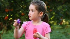 Ευτυχείς φυσαλίδες σαπουνιών παιδιών φυσώντας στο πάρκο απόθεμα βίντεο