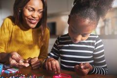Ευτυχείς χάντρες εκμετάλλευσης γυναικών για το χαριτωμένο παιδί Στοκ Εικόνες