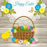 Ευτυχείς χαιρετισμοί Πάσχας - καλάθι Πάσχας με τα αυγά, κίτρινο κοτόπουλο, λουλούδια στο ξύλινο υπόβαθρο Στοκ Φωτογραφία