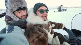 Ευτυχείς χαμογελώντας δύο τύποι στο όχημα για το χιόνι έχουν έναν γύρο στην Αρκτική απόθεμα βίντεο