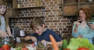 Ευτυχείς χαμογελώντας γονείς που εξετάζουν τα παιδιά που κόβουν τα λαχανικά μαζί στα οικογενειακά μαγειρεύοντας τρόφιμα κουζινών  απόθεμα βίντεο