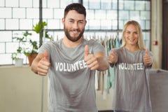 Ευτυχείς χαμογελώντας εθελοντές που δίνουν τους αντίχειρες Στοκ φωτογραφία με δικαίωμα ελεύθερης χρήσης