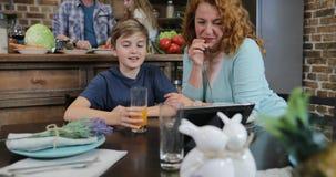Ευτυχείς χαμογελώντας μητέρα και γιος που χρησιμοποιούν τη συνεδρίαση υπολογιστών ταμπλετών στο χρόνο επιτραπέζιων εξόδων κουζινώ φιλμ μικρού μήκους