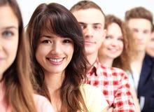 Ευτυχείς χαμογελώντας σπουδαστές που στέκονται στον υπόλοιπο κόσμο στοκ εικόνα