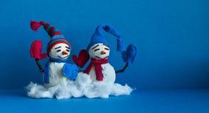 Ευτυχείς χιονάνθρωποι στο μπλε υπόβαθρο Χαρακτήρες χειμερινών παραδοσιακοί χιονανθρώπων με τα γάντια μαντίλι και τα αστεία καπέλα στοκ εικόνα με δικαίωμα ελεύθερης χρήσης