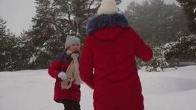 Ευτυχείς χιονιές παιχνιδιού παιδιών στο δάσος και το γέλιο πεύκων Εύθυμο παιχνίδι κοριτσιών εφήβων με το χιόνι το χειμώνα στο πάρ απόθεμα βίντεο