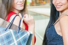 Ευτυχείς ψωνίζοντας γυναίκες κινηματογραφήσεων σε πρώτο πλάνο με τσάντες στο εμπορικό κέντρο Στοκ Φωτογραφίες
