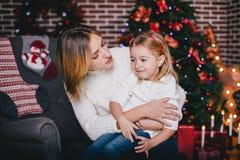 Ευτυχείς όμορφες μητέρα και αυτή λίγη τοποθέτηση κορών κοντά στο χριστουγεννιάτικο δέντρο σε ένα εσωτερικό διακοπών Στοκ φωτογραφία με δικαίωμα ελεύθερης χρήσης