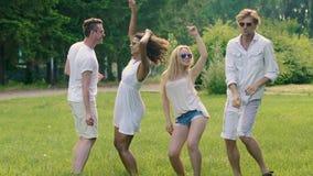 Ευτυχείς όμορφοι άνδρες που χορεύουν με τις flirty όμορφες γυναίκες στο υπαίθριο θερινό κόμμα απόθεμα βίντεο