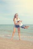 Ευτυχείς όμορφοι μητέρα και γιος που απολαμβάνουν το χρόνο παραλιών Στοκ Εικόνα