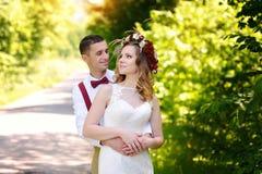 Ευτυχείς όμορφοι νύφη και νεόνυμφος που περπατούν στον τομέα στον ήλιο Στοκ Εικόνες