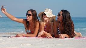 Ευτυχείς όμορφοι φίλοι που βρίσκονται στην πετσέτα και που παίρνουν ένα selfie στην παραλία απόθεμα βίντεο