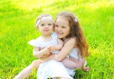 Ευτυχείς δύο αδελφές παιδιών στη χλόη το καλοκαίρι Στοκ Φωτογραφίες