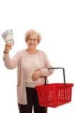 Ευτυχείς ώριμες δέσμες εκμετάλλευσης γυναικών των χρημάτων και του καλαθιού αγορών Στοκ Εικόνα