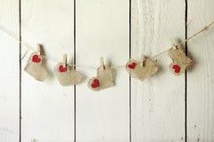 Ευτυχείς Burlap βαλεντίνων καρδιές που κρεμούν σε έναν ξύλινο τοίχο στοκ εικόνα