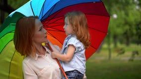 Ευτυχείς mom και κόρη κάτω από τη χρωματισμένη ομπρέλα φιλμ μικρού μήκους