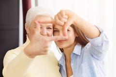 Ευτυχείς mom και κόρη που κάνουν το πλαίσιο με τα δάχτυλα στοκ εικόνες με δικαίωμα ελεύθερης χρήσης